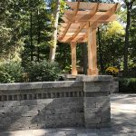 A stone wall with a pergola entrance in Northville MI
