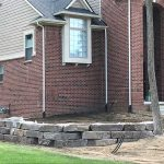 Use stones to create a retaining wall for a raised flower bed in Novi MI